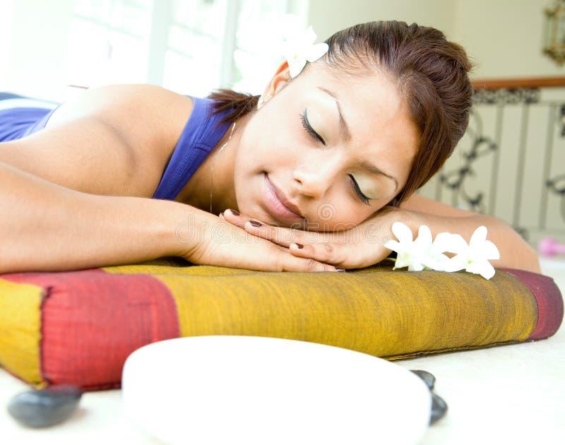 Junge Frau, die auf Massagebett stillsteht lizenzfreies stockfoto