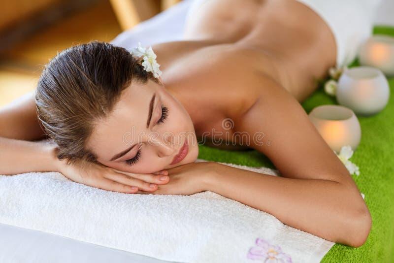 Junge Frau, die auf Massagetabelle und -aufwartung liegt lizenzfreies stockbild