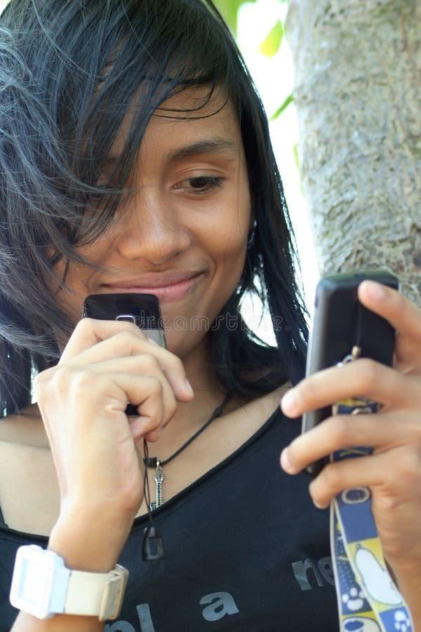 Junge Frau, die auf Mobile lächelt stockfotografie