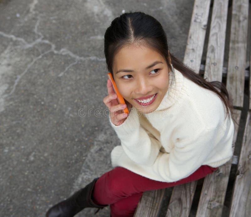 Junge Frau, die auf Parkbank sitzt und durch Handy nennt stockfotos