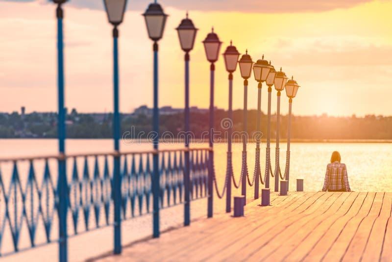 Junge Frau, die auf Pier bei Sonnenuntergang sitzt stockfotos