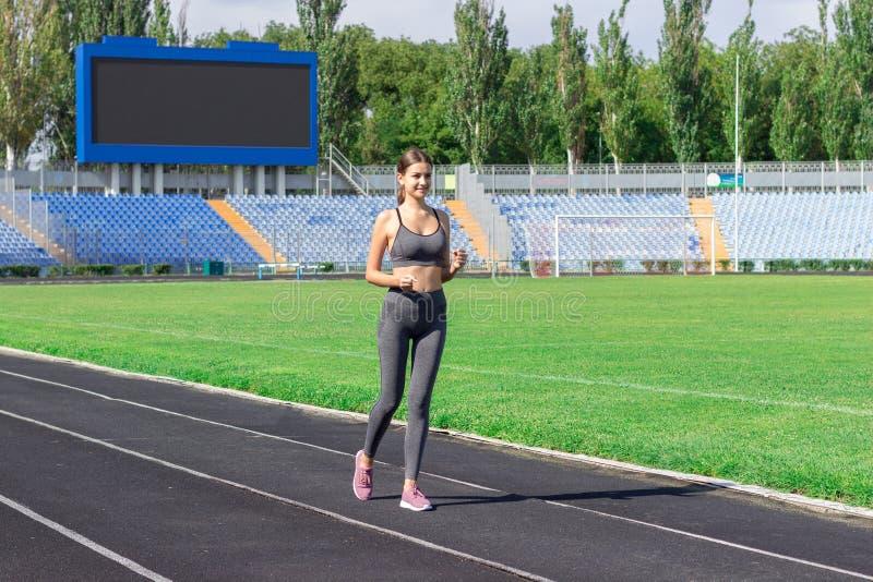 Junge Frau, die auf Rennbahnstadion läuft Zeit morgens ausbilden Leute tragen und Eignungskonzept zur Schau lizenzfreie stockfotografie