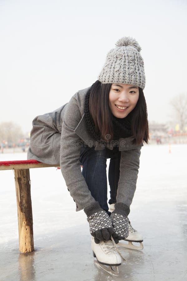 Junge Frau, die auf Schlittschuh, Peking sich setzt lizenzfreies stockfoto