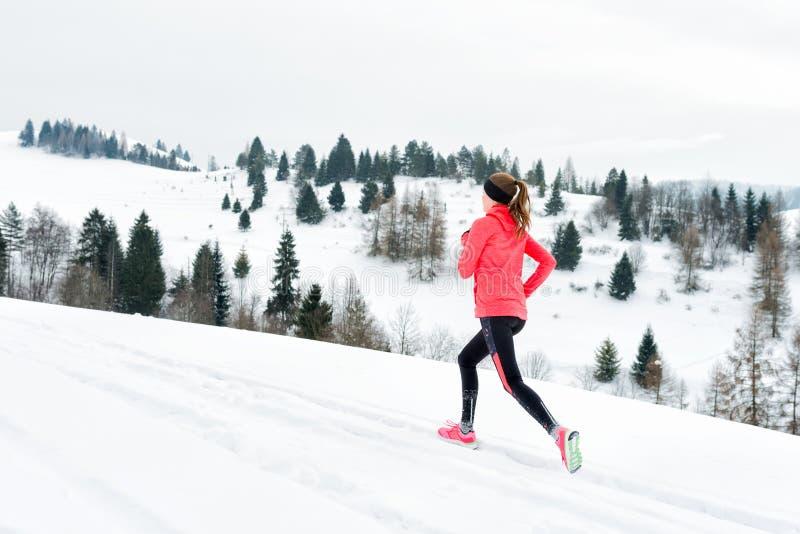 Junge Frau, die auf Schnee in den Winterbergen tragen warme Kleidungshandschuhe im Schneewetter läuft stockfotos