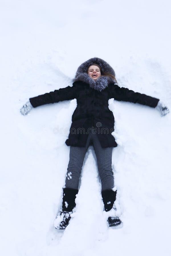 Junge Frau, die auf Schnee legt lizenzfreie stockfotos