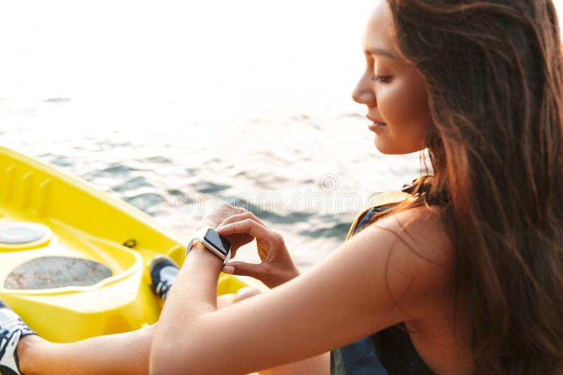 Junge Frau, die auf Seemeer im Boot unter Verwendung der Uhr Kayak fährt stockbilder