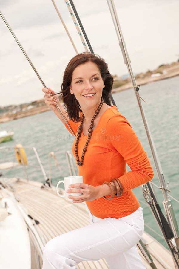 Junge Frau, die auf Segelnboot steht lizenzfreie stockbilder