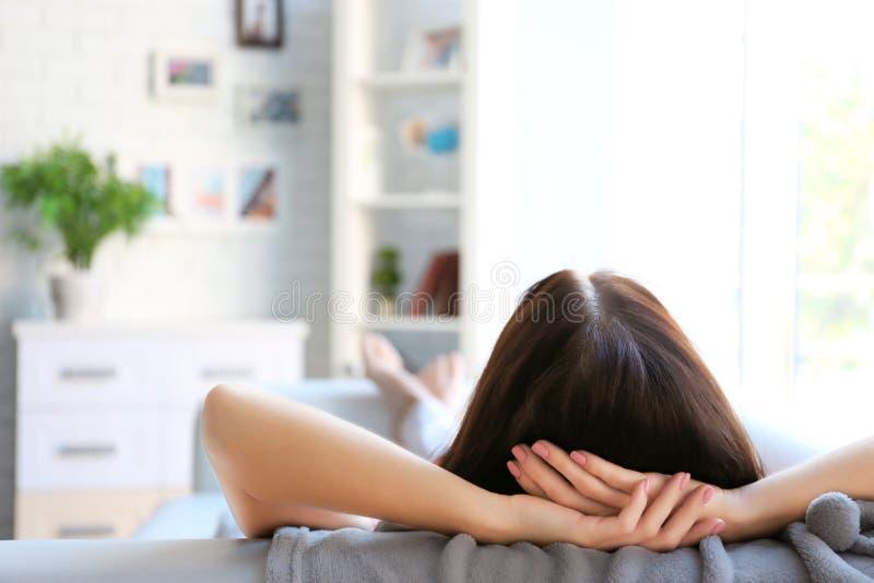 Junge Frau, die auf Sofa schläft stockbild