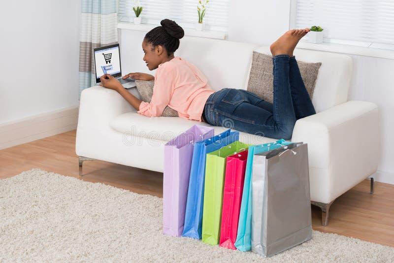Junge Frau, die auf Sofa Shopping Online liegt lizenzfreies stockfoto