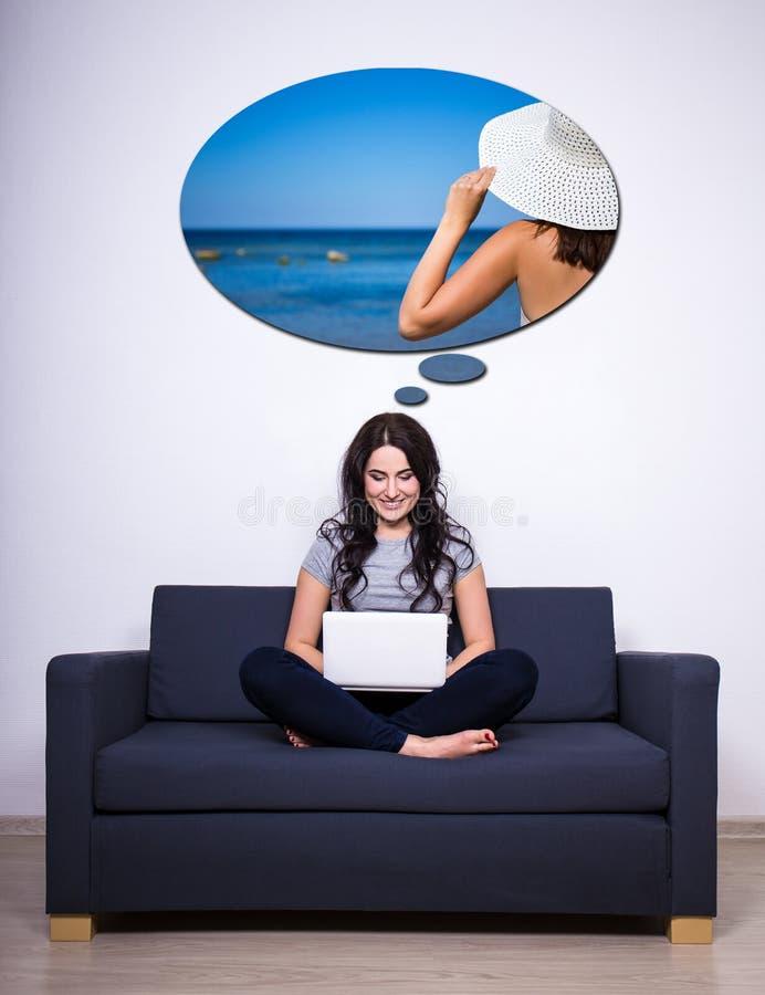 Junge Frau, die auf Sofa, unter Verwendung des Laptops sitzt und über Summe träumt lizenzfreies stockbild