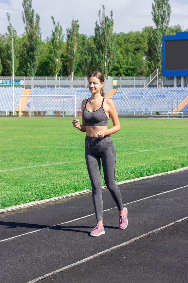 Junge Frau, die auf Stadionsbahn am sonnigen Morgen läuft Leute tragen und Eignungskonzept zur Schau stockbild