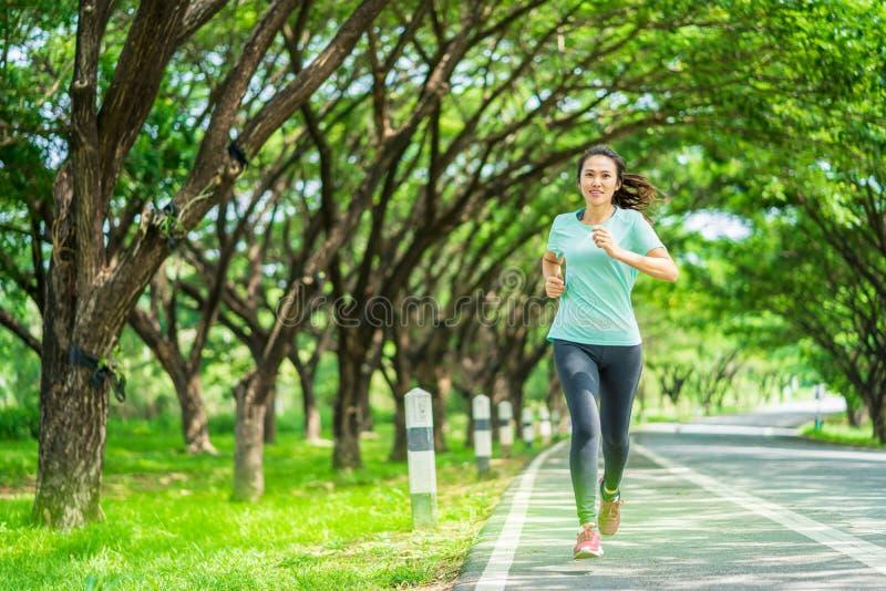 Junge Frau, die auf Straße in der Natur läuft lizenzfreie stockbilder