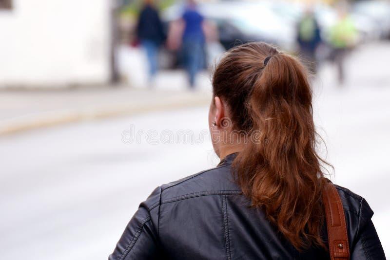 Junge Frau, die auf Straße geht stockfotos