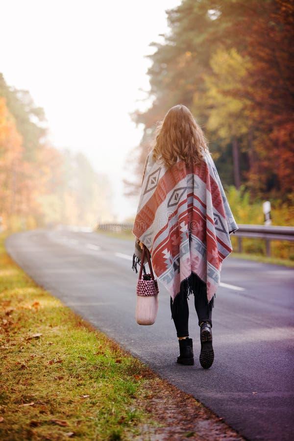 Junge Frau, die auf Straße im Herbst geht lizenzfreie stockfotografie