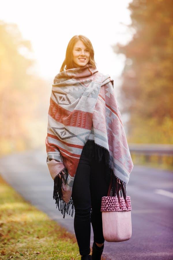 Junge Frau, die auf Straße im Herbst geht lizenzfreies stockfoto