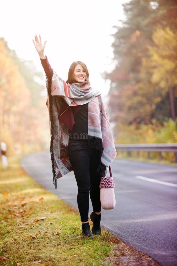 Junge Frau, die auf Straße im Herbst und im Wellenartig bewegen geht stockfoto