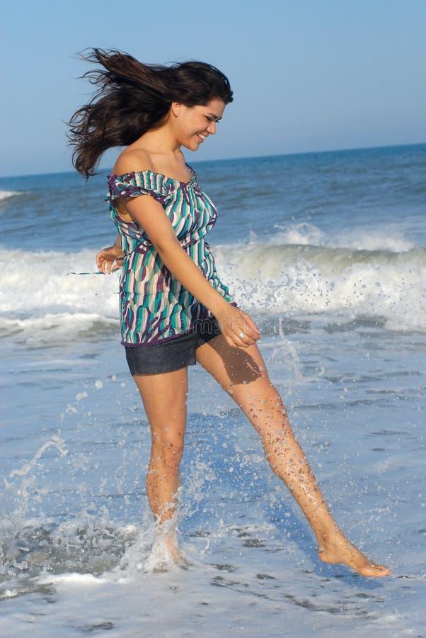Junge Frau, die auf Strand geht stockfotografie
