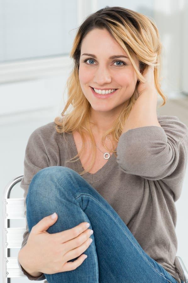 Junge Frau, die auf Stuhl sitzt lizenzfreies stockfoto