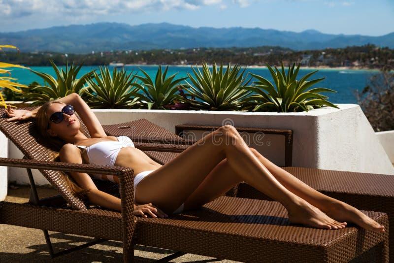 Junge Frau, die auf sunbed ein Sonnenbad nimmt lizenzfreie stockfotografie