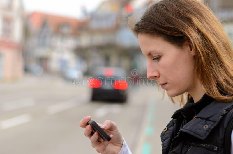 Junge Frau, die auf Textnachrichten überprüft stockbilder