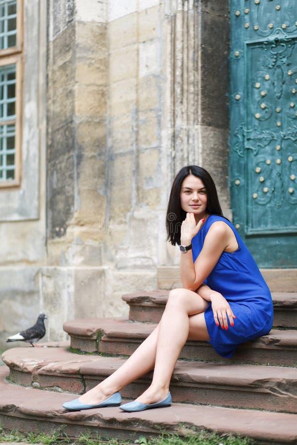 Junge Frau, die auf Treppe des alten antiken Gebäudes sitzt stockbilder