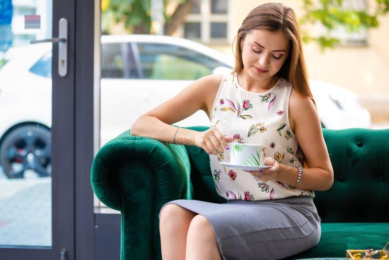 Junge Frau, die auf trinkendem Tee des Sofas von der Schale in einem Büro sitzt lizenzfreies stockbild