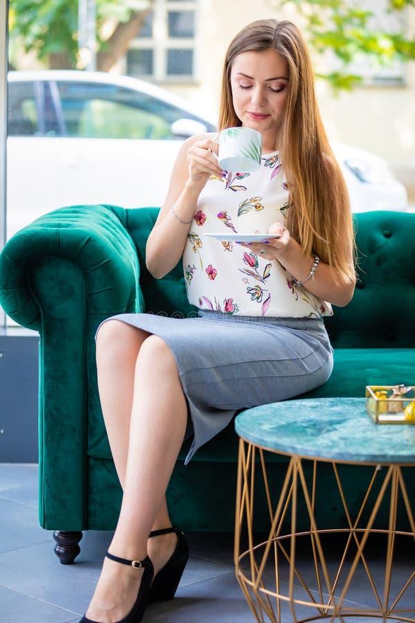 Junge Frau, die auf trinkendem Tee des Sofas von der Schale in einem Büro sitzt stockfotos