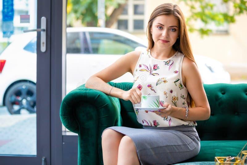 Junge Frau, die auf trinkendem Tee des Sofas von der Schale in einem Büro sitzt stockbild