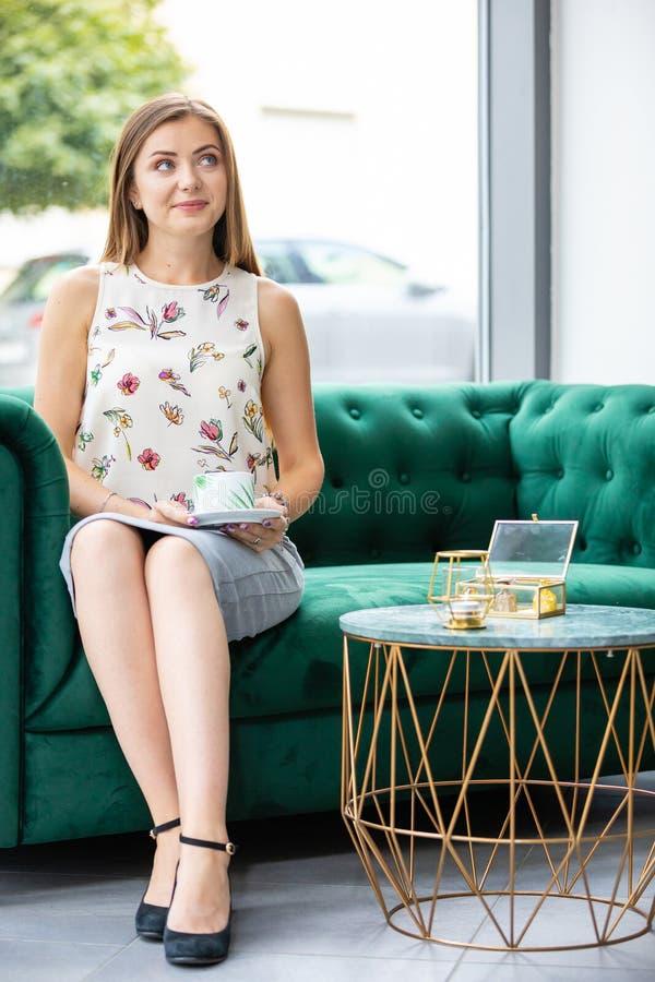 Junge Frau, die auf trinkendem Tee des Sofas von der Schale in einem Büro sitzt lizenzfreies stockfoto