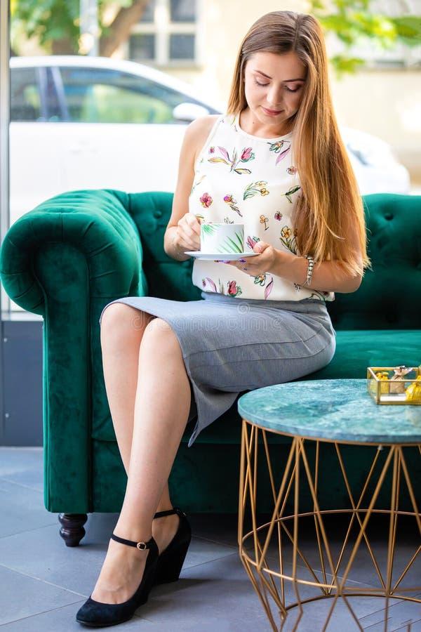 Junge Frau, die auf trinkendem Tee des Sofas von der Schale in einem Büro sitzt stockbilder