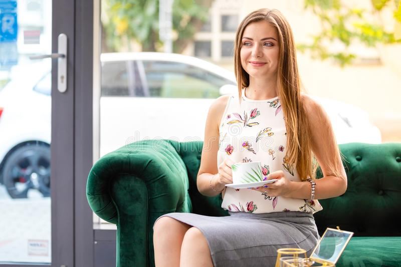 Junge Frau, die auf trinkendem Tee des Sofas von der Schale in einem Büro sitzt lizenzfreie stockfotografie