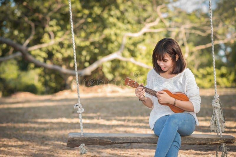 Junge Frau, die auf Ukulele spielt stockfoto