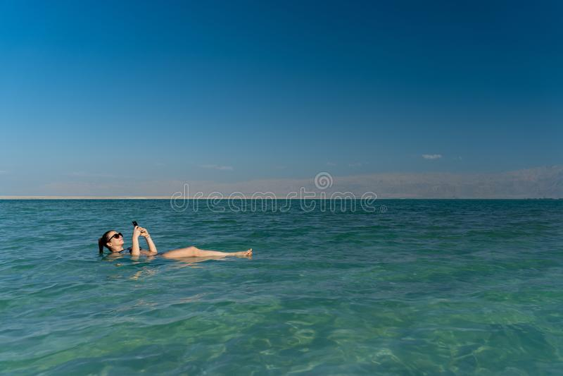 Junge Frau, die auf die Wasseroberfl?che des Toten Meers schwimmt und ihren Smartphone verwendet lizenzfreies stockfoto