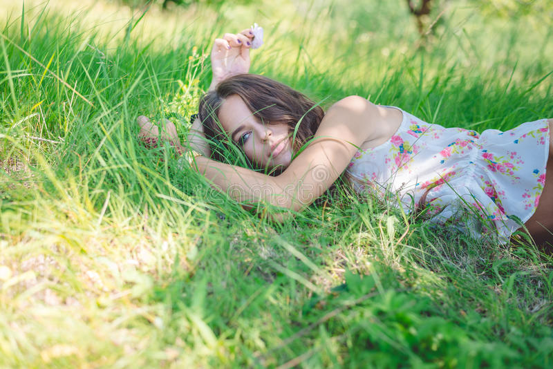 Junge Frau, die auf weichem frischem Frühlingsgras liegt stockfotografie