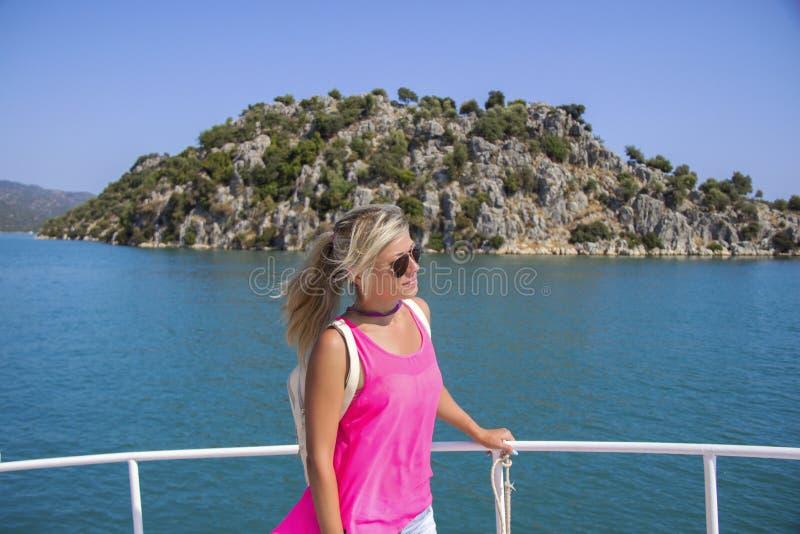 Junge Frau, die auf Yacht am sonnigen Tag steht und zu einem Meer schaut lizenzfreies stockfoto