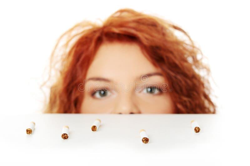 Junge Frau, die auf Zigaretten schaut lizenzfreie stockbilder