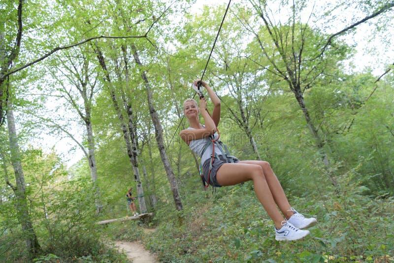 Junge Frau, die auf zipline im Wald absteigt lizenzfreie stockfotografie