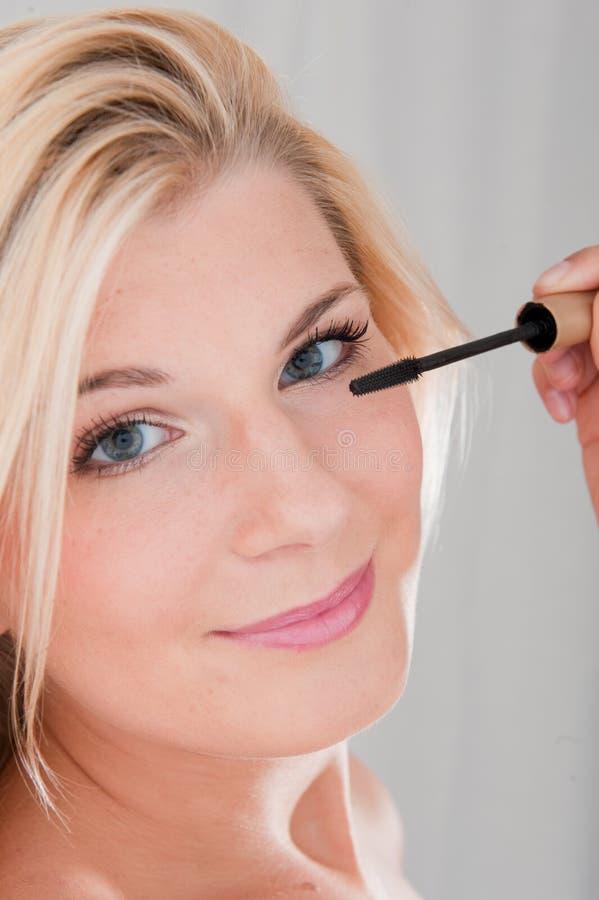 Junge Frau, die Augeenwimperntusche anwendet lizenzfreie stockbilder