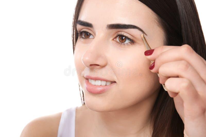 Junge Frau, die Augenbrauen mit Pinzette zupft lizenzfreie stockfotografie