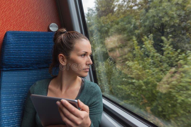 Junge Frau, die aus dem Fenster heraus schaut und eine Tablette für das Studieren beim Reisen mit dem Zug verwendet lizenzfreie stockfotografie