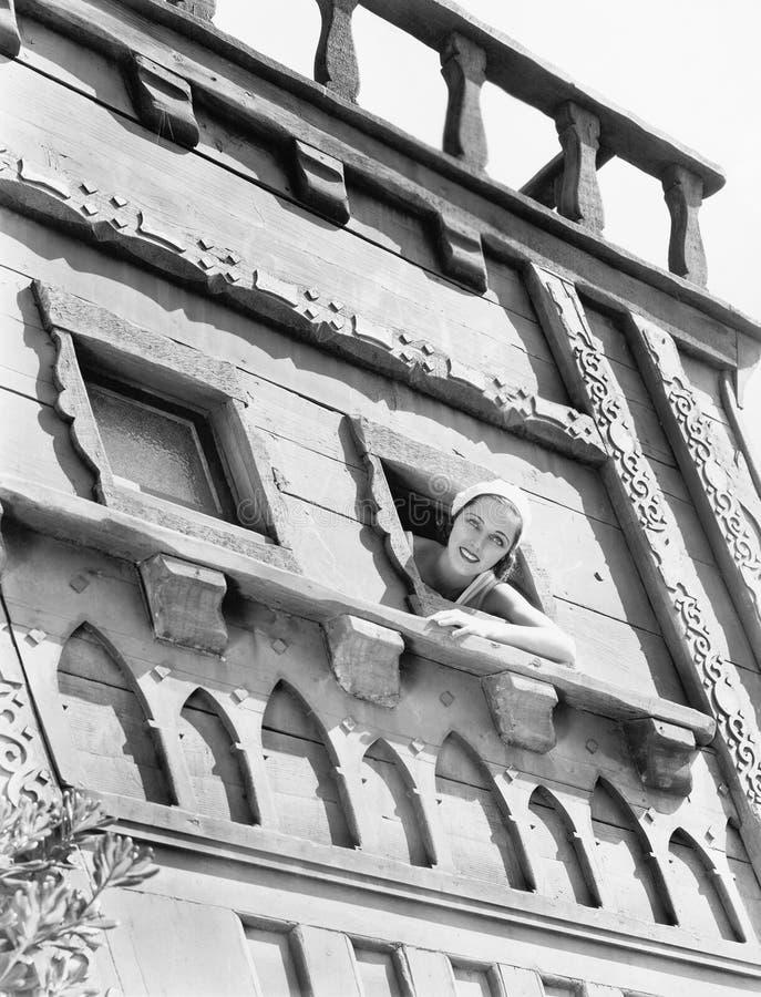 Junge Frau, die aus einem Fenster eines Schlosses heraus schaut (alle dargestellten Personen sind nicht längeres lebendes und kei stockbild