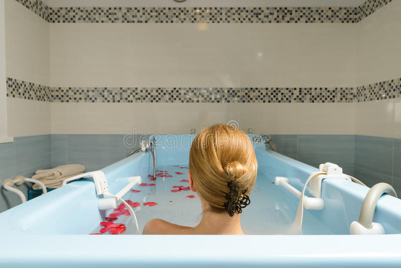 Junge Frau, die Bad mit Milch und den rosafarbenen Blumenblättern nimmt lizenzfreie stockfotos