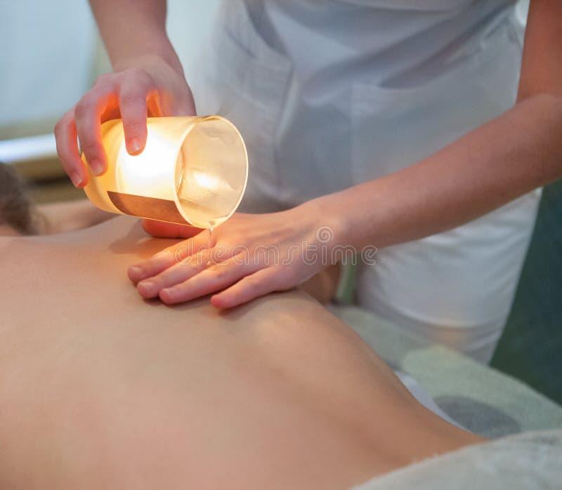 Junge Frau, die Badekurortmassage mit Massagekerze erhält lizenzfreie stockfotografie
