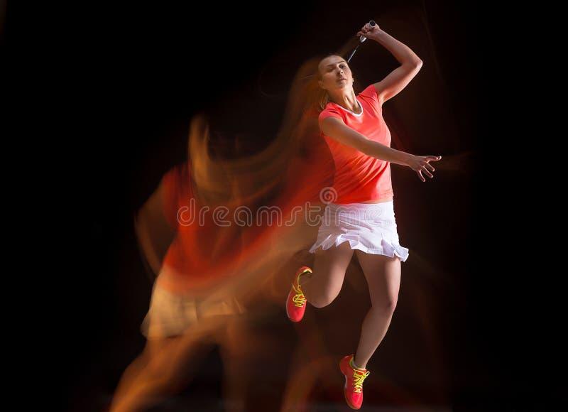 Junge Frau, die Badminton über schwarzem Hintergrund spielt lizenzfreies stockfoto