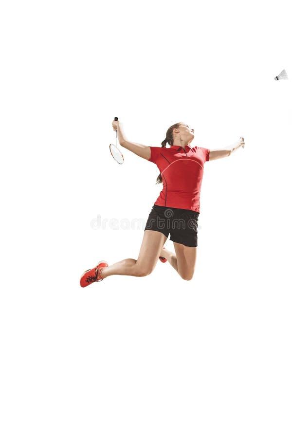 Junge Frau, die Badminton über weißem Hintergrund spielt stockbilder