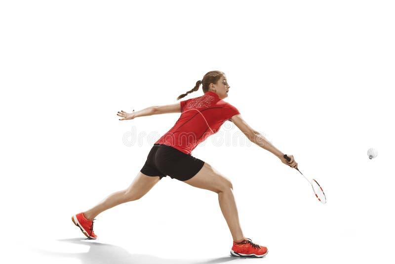 Junge Frau, die Badminton über weißem Hintergrund spielt lizenzfreies stockbild