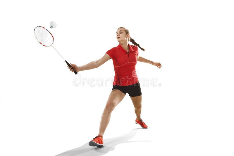 Junge Frau, die Badminton über weißem Hintergrund spielt lizenzfreies stockfoto
