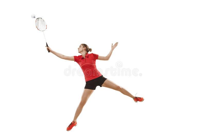 Junge Frau, die Badminton über weißem Hintergrund spielt lizenzfreie stockfotografie