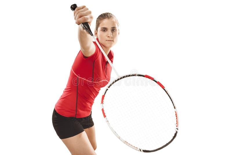 Junge Frau, die Badminton über weißem Hintergrund spielt lizenzfreie stockbilder