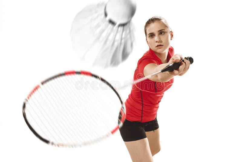 Junge Frau, die Badminton über weißem Hintergrund spielt stockfotografie
